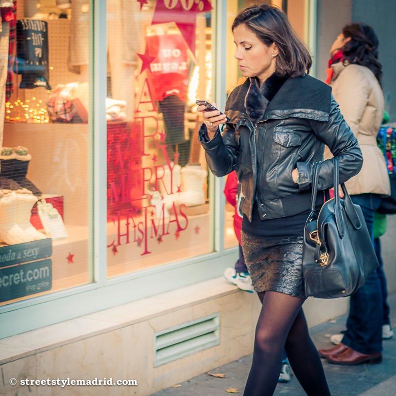 Street Style Madrid, cazadora de cuero negra, con falda de piel negra, medias negras y bolso negro