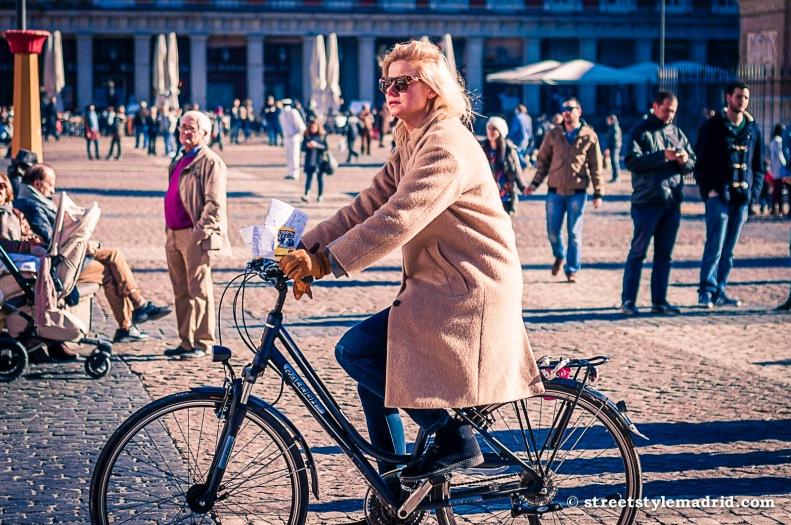 Street Style Madrid, abrigo camel en bicicleta, con vaqueros y gafas de sol