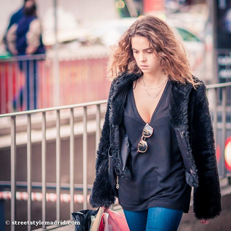 Street Style Madrid, cazadora de pelo, gafas de sol, camiseta negra y vaqueros.