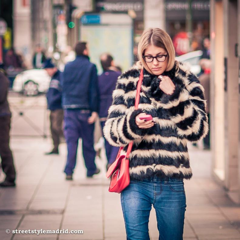 Street Style Madrid, vaqueros con abrigo de pelo a rayas, bolso rojo y gafas.